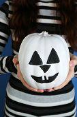 Woman holding decorative pumpkin, close-up
