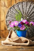 Bright wildflowers in bucket on wooden background