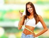 Shopping concept. Beautiful young woman with green apples and measure tape on shop background