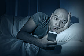 image of addicted  - young cell phone addict man awake at night in bed using smartphone for chatting flirting and sending text message in internet addiction and mobile abuse concept - JPG