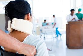 foto of neck brace  - Brunette woman with a neckbrace sitting on wheelchair in hospital - JPG