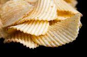 picture of crisps  - Ridged fried potato crisps on black surface - JPG