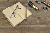 pic of spyglass  - Open Vintage Notebook With Blank Pages Gold Fountain Pen Glasses Retro Magnifier Compass and Spyglass On Grunge Woodeen Table Background - JPG