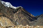 stock photo of jammu kashmir  - Rocky landscape of with ice peaks in background dark blue sky Ladakh Jammu and Kashmir India - JPG