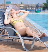 pic of sunbathers  - Young woman in bikini and hat in swimsuit laying on chaise - JPG