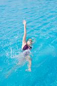 stock photo of crawling  - Young girl in goggles and cap swimming back crawl stroke style in the blue water pool - JPG