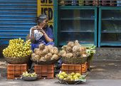 Woman Sells Coconuts And Bananas.
