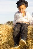 foto of haystack  - Country boy in national costume plays in a haystack - JPG