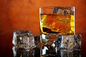 foto of whiskey  - Glass of whiskey and ice cubes on dark reflective table  - JPG