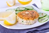 foto of patty-cake  - Close up of a salmon patty served woth cucumber and lemon - JPG
