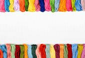 stock photo of canvas  - Colorful cotton craft threads on white canvas with copy space - JPG