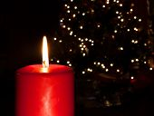 stock photo of candle flame  - Red candle with a flame with a Christmas tree behind  - JPG