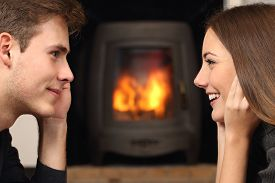 image of flirt  - Side view of a couple flirting and looking each other in front a fireplace - JPG