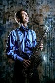 image of saxophones  - Portrait of a musician with his saxophone - JPG