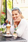 foto of frappe  - A picture of a happy woman drinking frappe in cafe  - JPG