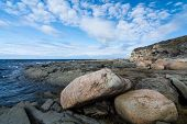stock photo of labradors  - Rocks and seaweed cover the shore of a bay in the province of Newfoundland and Labrador - JPG