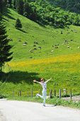 picture of pasture  - young woman standing on background of pastures with cows - JPG