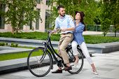 picture of opposites  - Young couple sitting on a bicycle opposite the green city park - JPG
