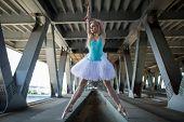 foto of tutu  - Graceful ballerina in white tutu in the industrial background of the bridge - JPG