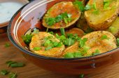 stock photo of oven  - Rustic oven baked potatoes with herbs on wooden table