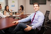 foto of laws-of-attraction  - Attractive young lawyer sitting in a meeting room with some of his co - JPG