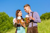 stock photo of pretzels  - German couple in Tracht with beer and pretzel - JPG