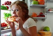 picture of sneak  - woman eats sweets at night to sneak in a refrigerator - JPG