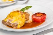 image of pork cutlet  - A breaded and baked pork cutlet with sauce and gravy mashed potatoes asparagus and broiled tomato - JPG