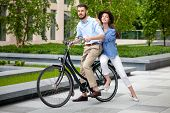 image of opposites  - Young couple sitting on a bicycle opposite the green city park - JPG