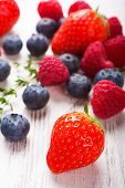 picture of berries  - Close up of strawberry and ather berries on White Wooden Background - JPG