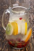 pic of pitcher  - Glass pitcher of homemade detox water enriched with cherries and frozen fruit wedges. Misted jug full of cold water with popsicles. Clean eating