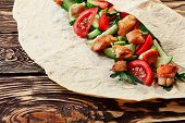 stock photo of shawarma  - Traditional shawarma wrap with chicken and vegetables on wooden table just before wrapping - JPG