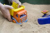 picture of hand truck  - Children hands playing with a toy truck in the sandbox outdoor shot with selective focus - JPG