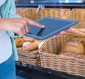 image of tong  - Woman using tablet pc against baskets with breads freshly baked and tongs - JPG