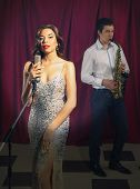 foto of singer  - Female singer and saxophonist performing at the jazz club - JPG