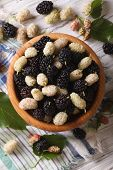 stock photo of mulberry  - White and black mulberries in a wooden bowl on the table close - JPG