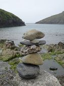 picture of inlet  - Pile of rocks within beach and cliffs coastal inlet seascape photographed at Port Quin in Cornwall