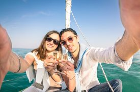 image of champagne color  - Young couple in love taking selfie on sailing boat cheering with champagne wine  - JPG