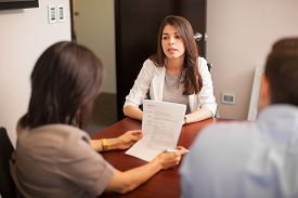 picture of pov  - Portrait of a young Hispanic woman sitting in front of two people during a job interview  - JPG