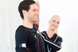 stock photo of stimulating  - Female coach giving man and woman ems electro muscular stimulation exercise  - JPG