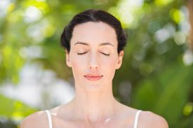 picture of ohm  - Portrait of a woman in a meditation position against a white backgrou - JPG