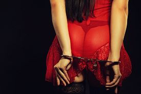 picture of handcuff  - Seductive woman in red sexy dress posing over dark background in handcuffs - JPG