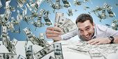 business, people, success and fortune concept - happy businessman with heap of dollar money over blu poster