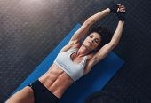 Woman Lying On Mat Doing Stretching Exercise poster