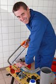 Smiling plumber sawing plastic pipe