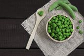 Wooden Bowl With Peas, Has Around A Wooden Spoon And Some Pods Of Peas, On A Wooden Board. In Horizo poster