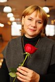 Smiling middleaged woman with red rose in hands stand in empty cafe