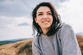 Portrait Of Happy And Funny Brunette Woman Smiling And Looking Away, Against Nature Meadow And Overc poster