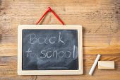 Back To School On Blackboard With Frame Hanging On Wooden Wall poster