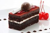 A slice of delicious black forest cake, garnished with all the goodies